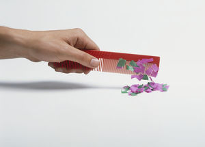 science technology/studio shot/hand holding red plastic comb pink green paper